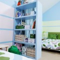 Wide view of blue and green decorated kid's room with blue shelf to store toys and items, striped wall with pastel blue and green colors, beds with new bedding, and storage boxes.