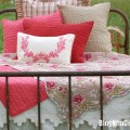 Pink and red cottage style bedding, pillows, floral bed cover, and metal bed frame.